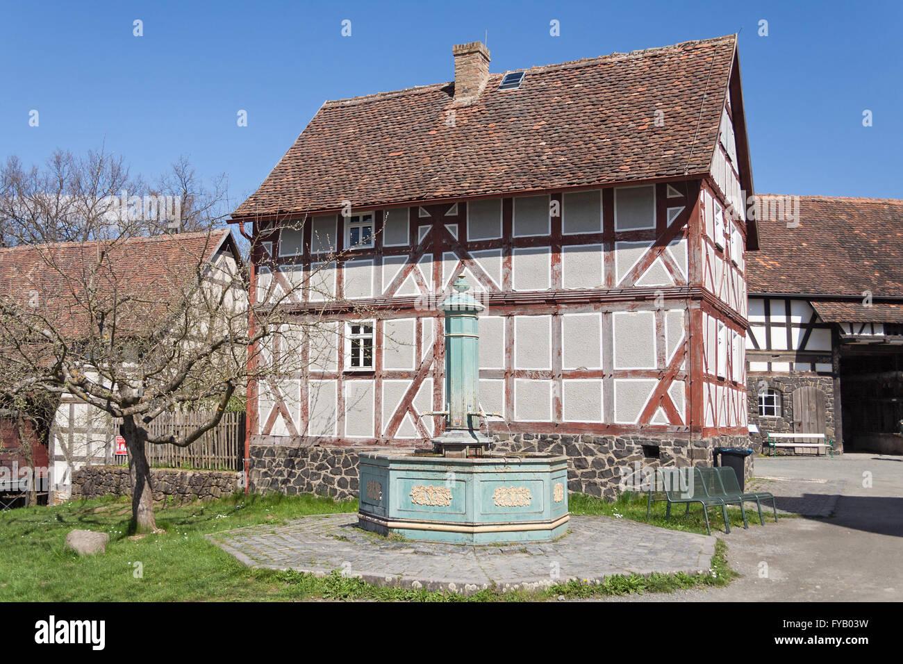 Alte halbe Fachwerkhaus mit Brunnen in das Freilichtmuseum Hessenpark Stockbild