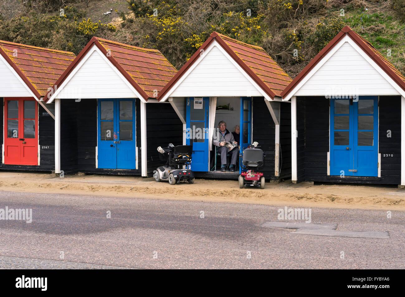 Älteres Ehepaar sitzen in einer öffentlichen Verleih Strandhütte mit paar Scooter geparkt außerhalb, Bournemouth, Stockfoto