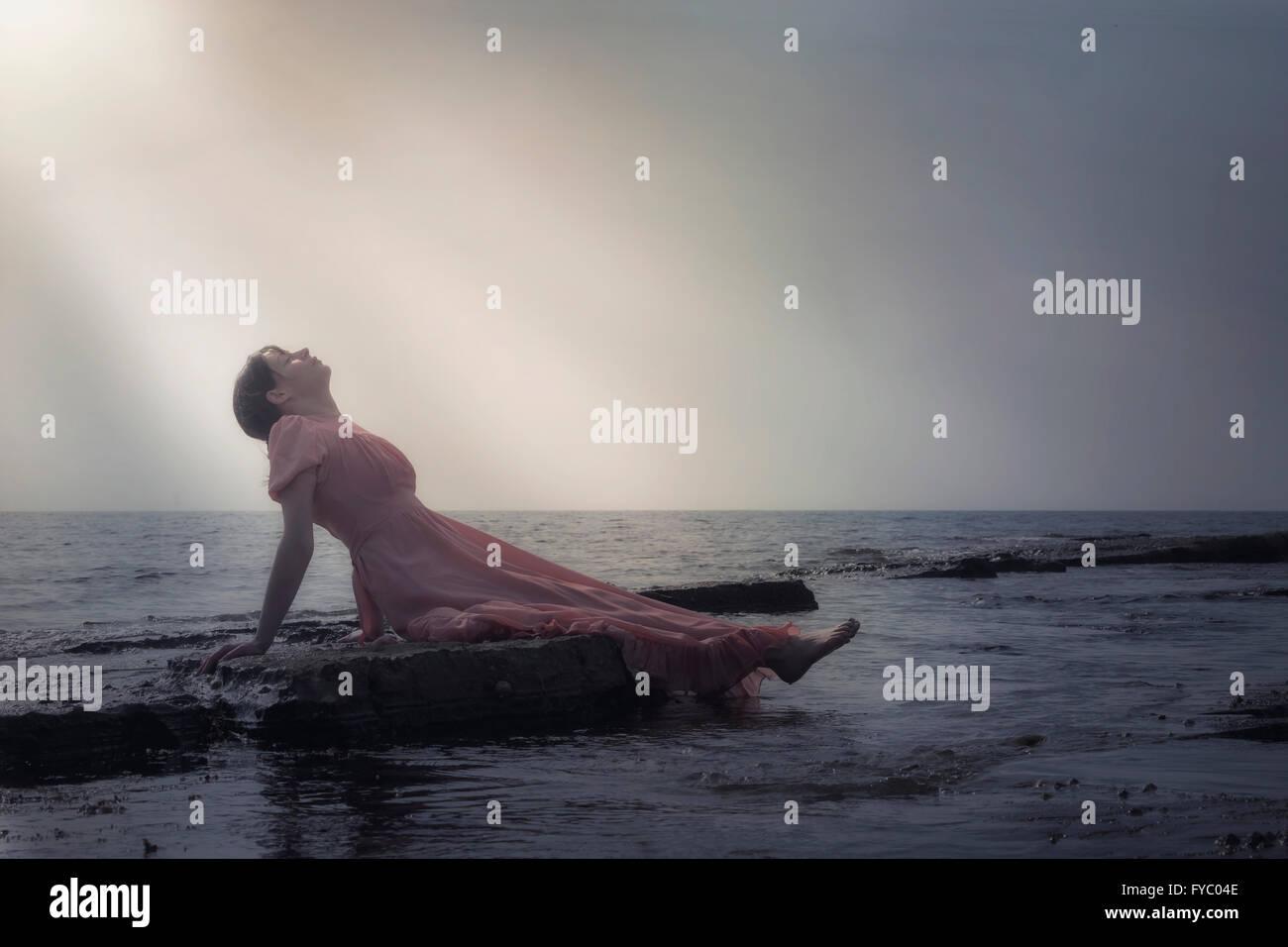 eine Frau in einem rosa Kleid ist auf den Steinen am Meer liegen. Stockbild