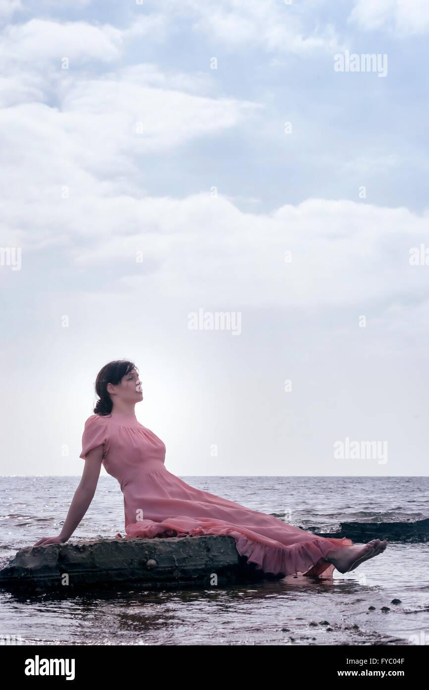 eine Frau in einem rosa Kleid sitzt auf Steinen am Meer Stockbild