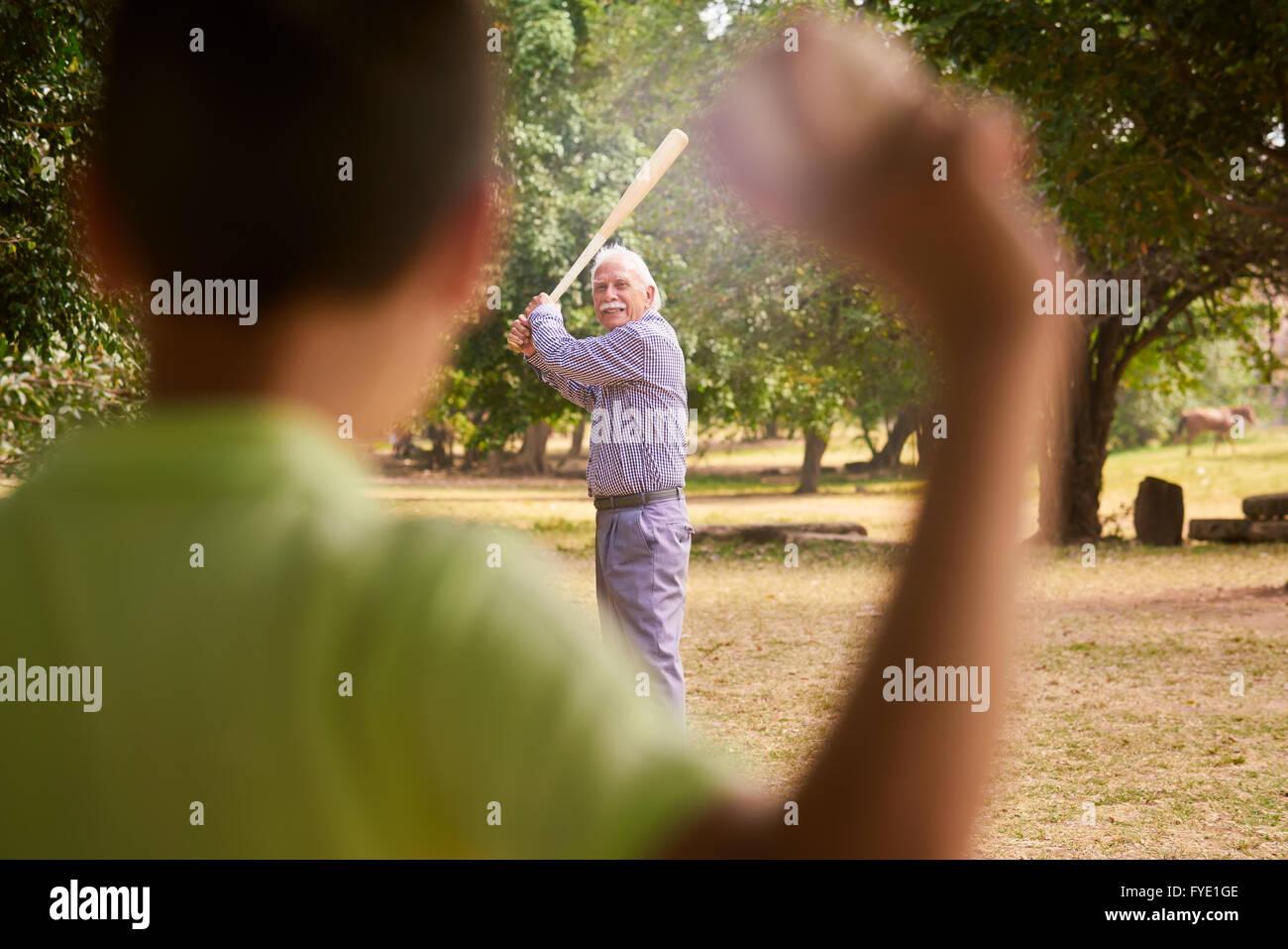 Großeltern mit Enkel: Senior Woman spielen Baseball mit seinem Enkel im Park. Der alte Mann hält die Fledermaus, Stockbild