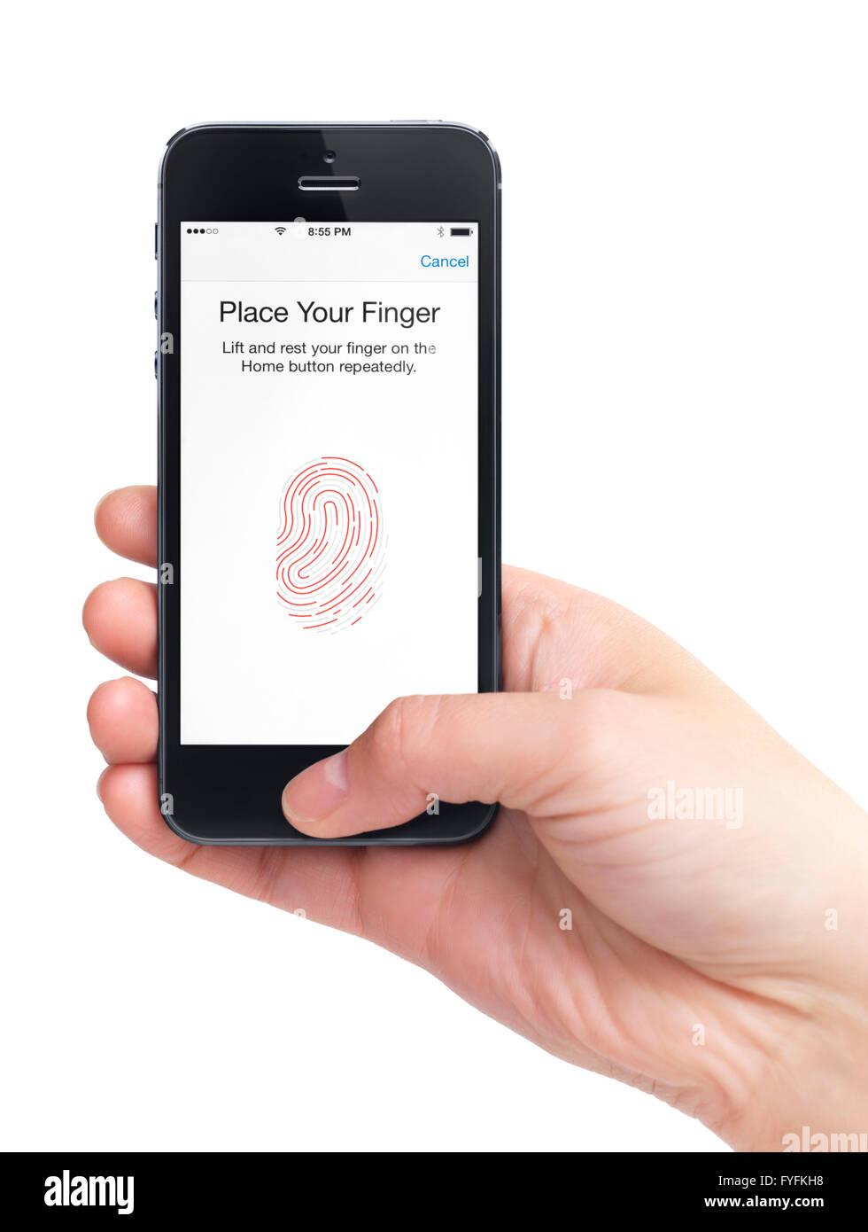 Hand, die ein iPhone 5 Konzept einer Fingerabdruck-Sensor-App Stockbild