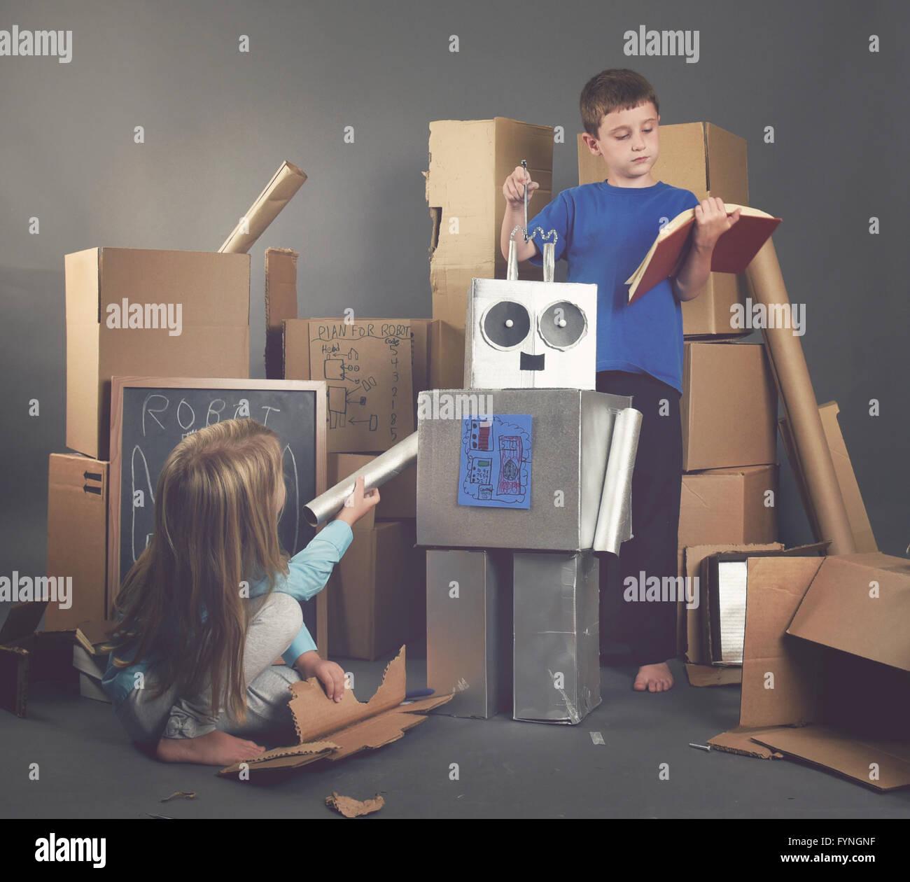 Zwei Kinder bauen einen Metall Roboter aus Pappkartons mit Werkzeugen und Bücher für eine Phantasie, Wissenschaft, Stockbild