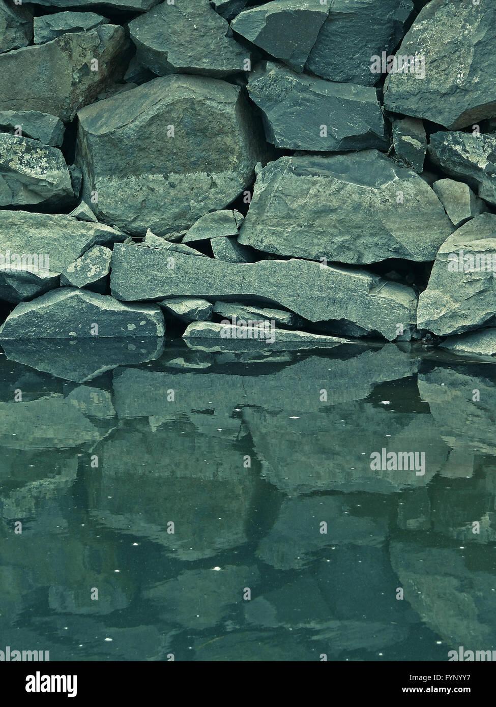 Reflexion von Steinen in ruhigem Wasser Stockbild