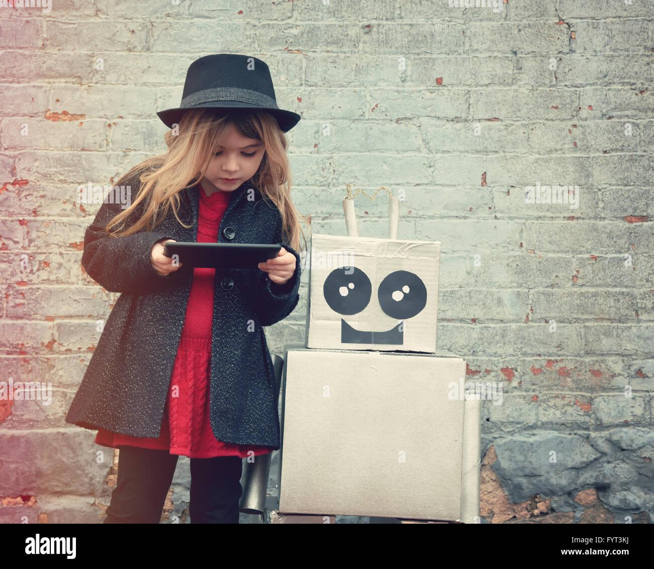 Ein kleines Hipster Kind trägt einen Hut und hält ein Tablet mit ihrem Roboter-Freund downtown für Stockbild