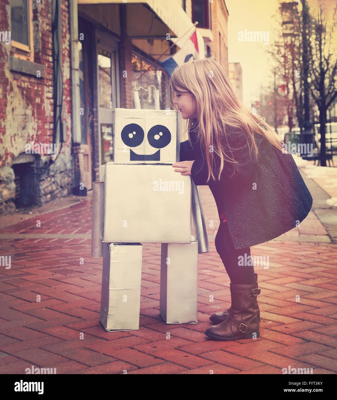 Ein kleines Mädchen umarmt einen Metall Pappen Roboter Innenstadt gegen eine Mauer außerhalb für Stockbild