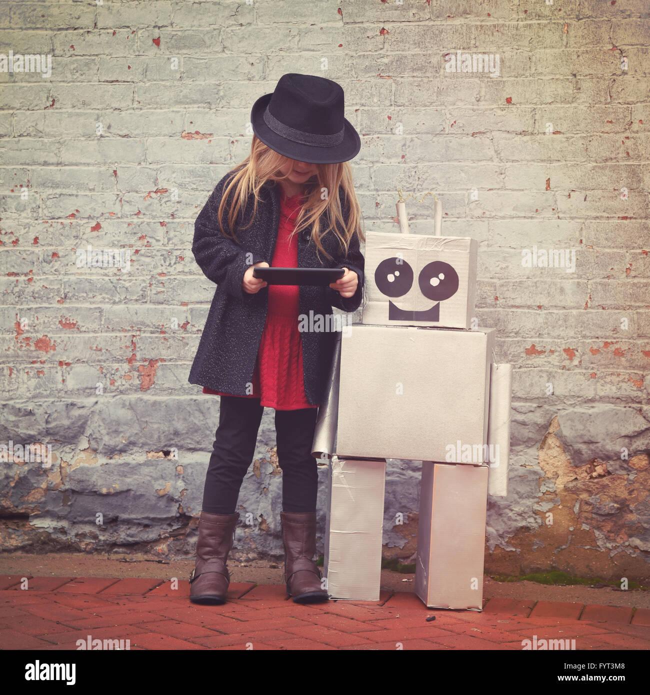 Ein kleines Hipster Kind tragen hält einen Tablet mit ihrem Spielzeug-Roboter-Freund Innenstadt für ein Stockbild