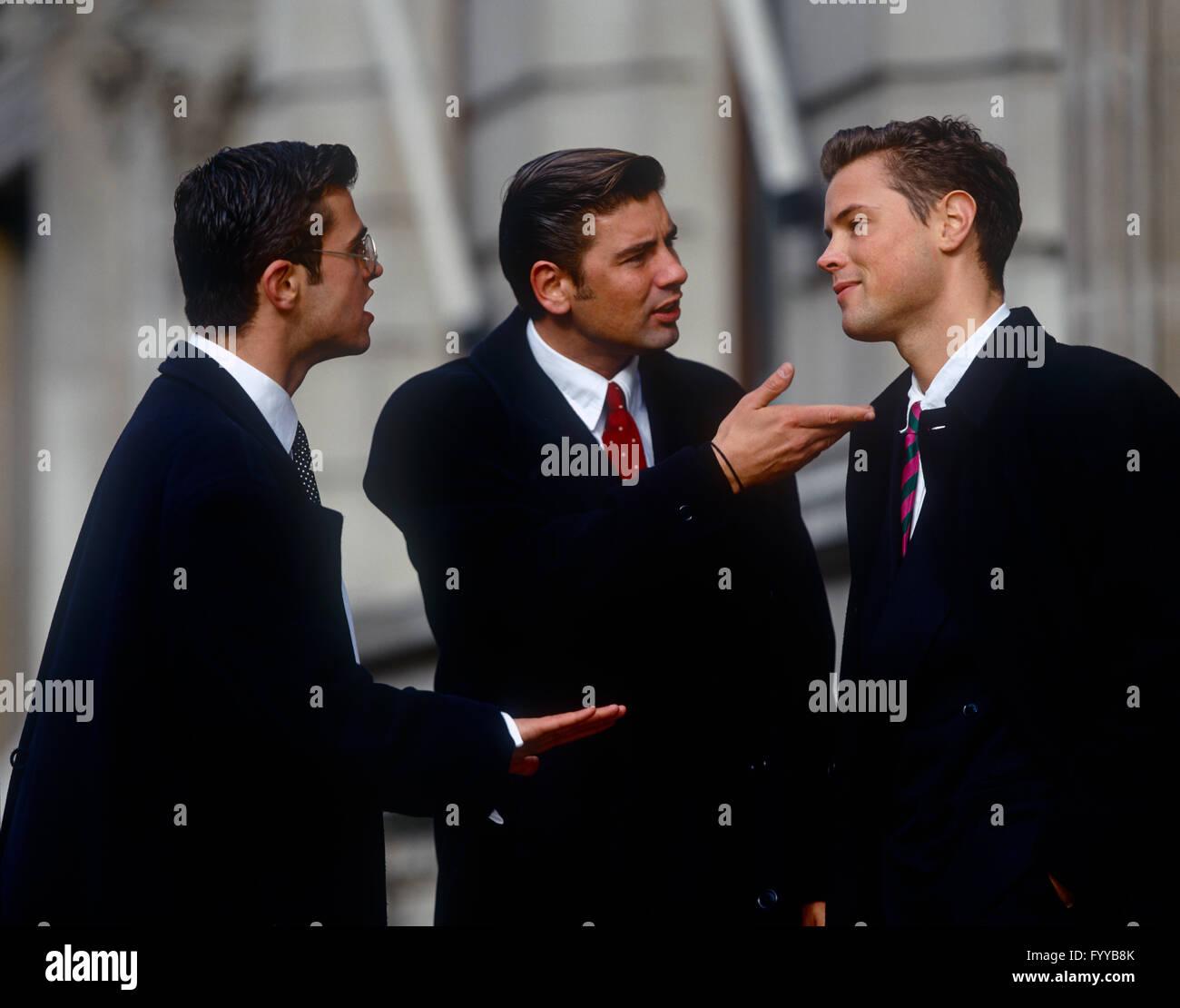 Drei Männer in intelligente Shirts haben eine Diskussion im Außenbereich. Stockbild