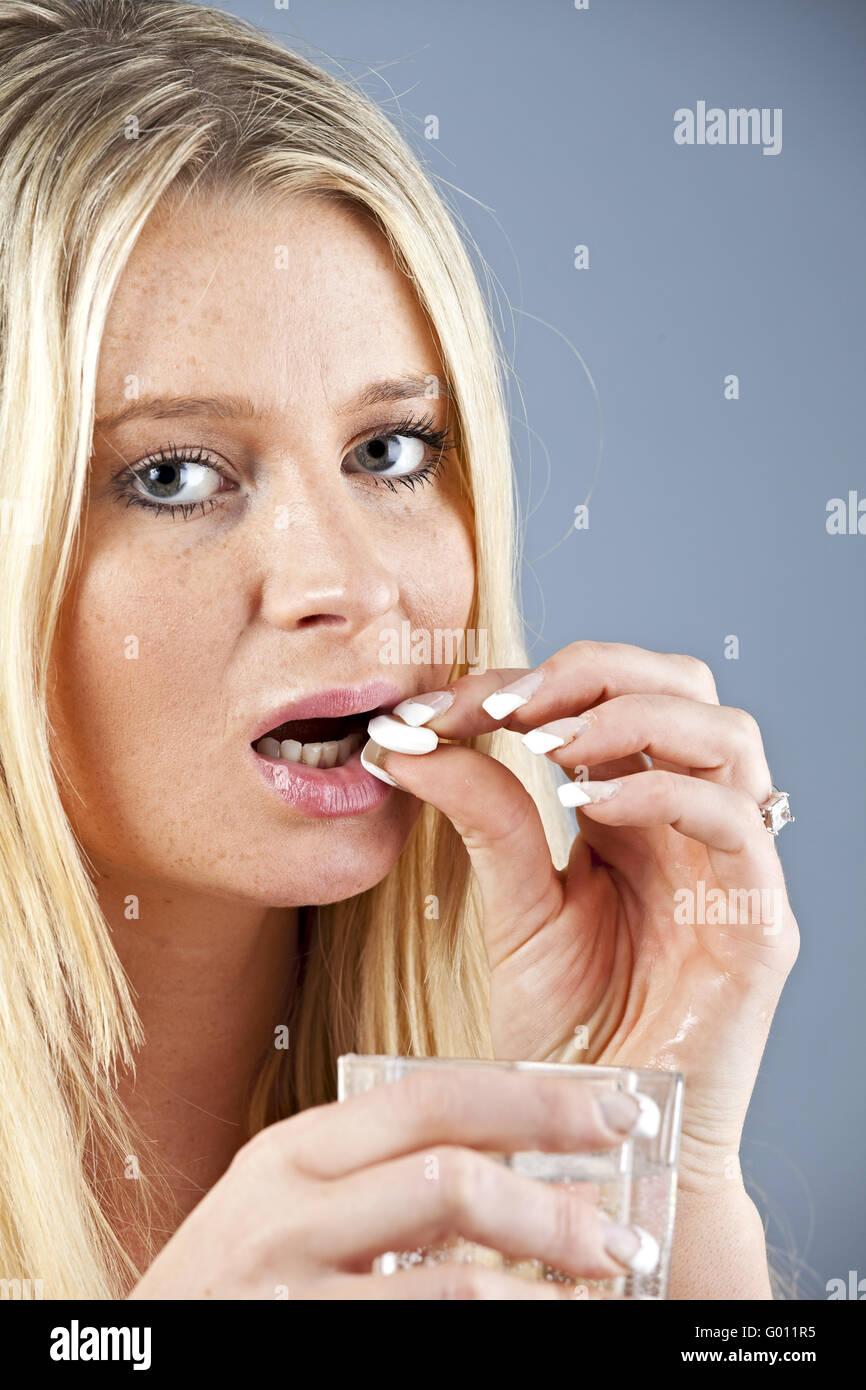 blonde Frau, die eine Pille mit einem Glas Wasser Stockbild