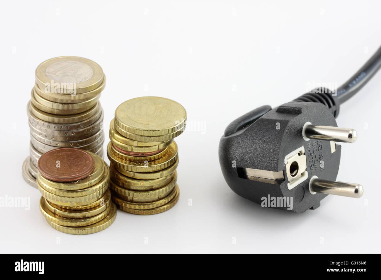 Münzen und einen Stecker als Symbol für Energiekosten Stockbild