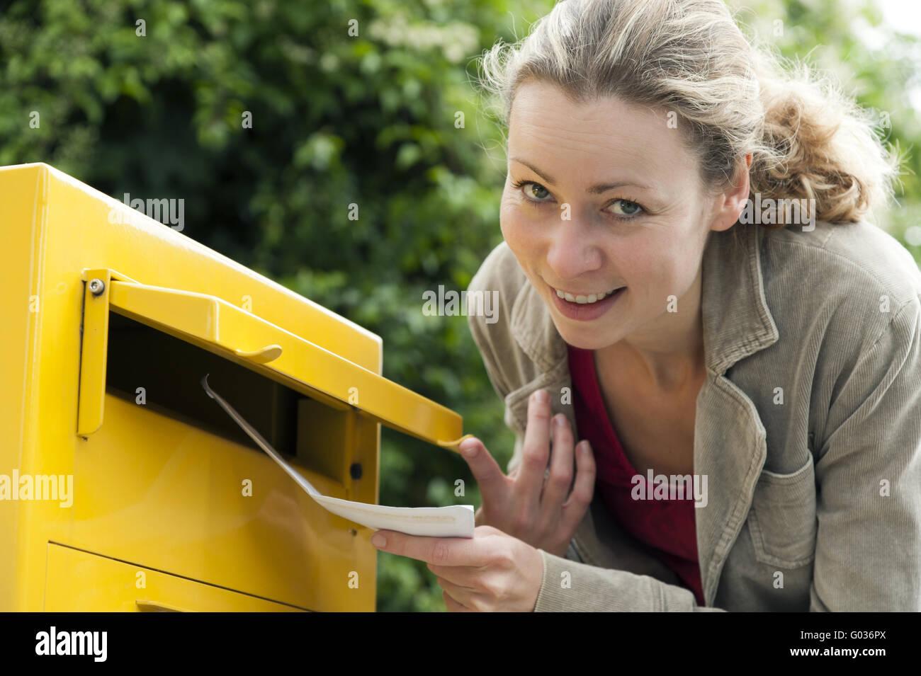 Junge Frau einen Brief in den Briefkasten werfen Stockbild