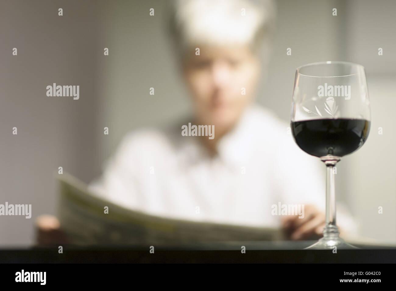 Lesende Frau mit einem Glas Wein sitzen an einem ta Stockbild