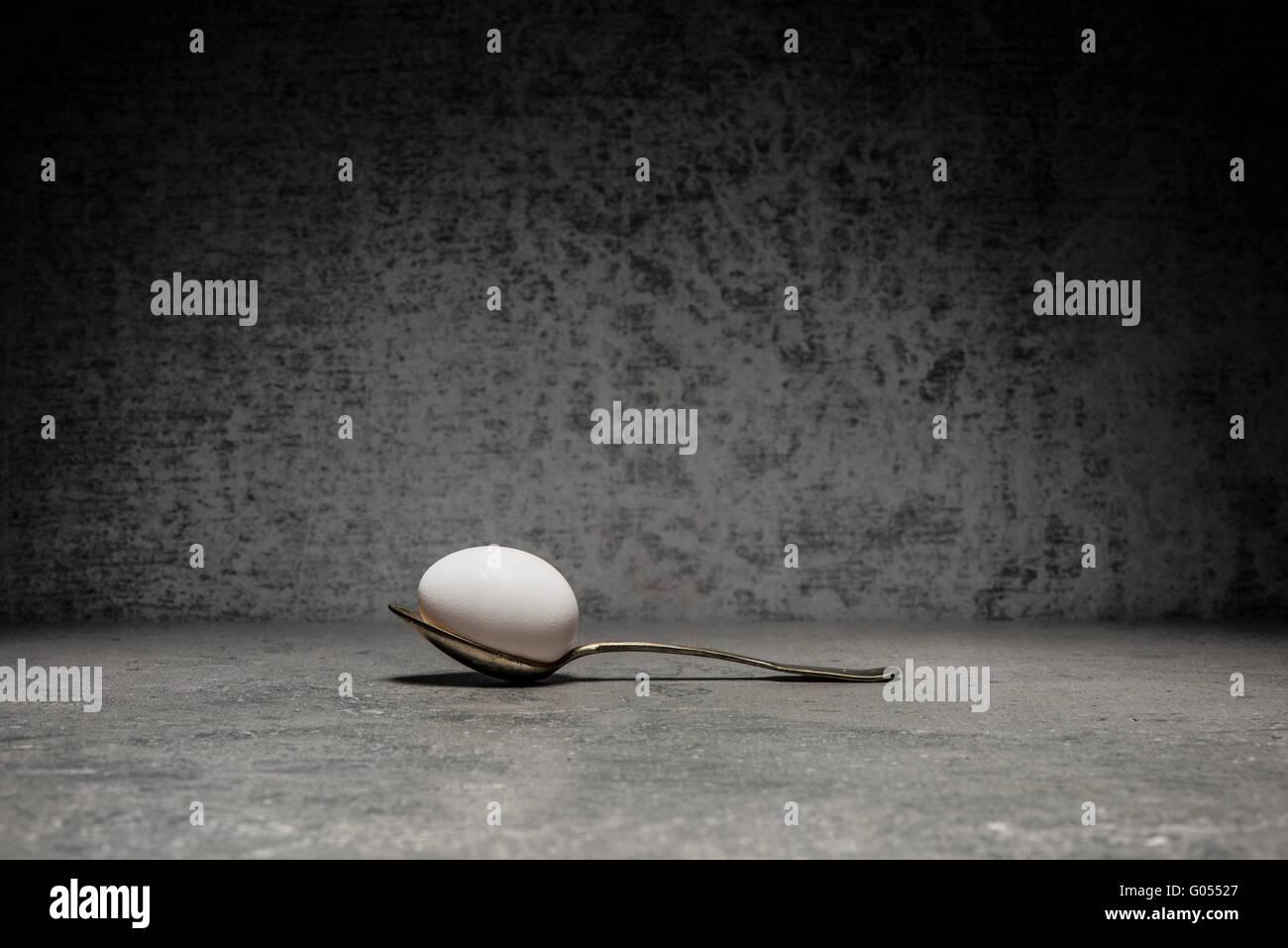 Ei und Löffel Stillleben. Konzeptbild mit Einfachheit und Kopie. Stockbild
