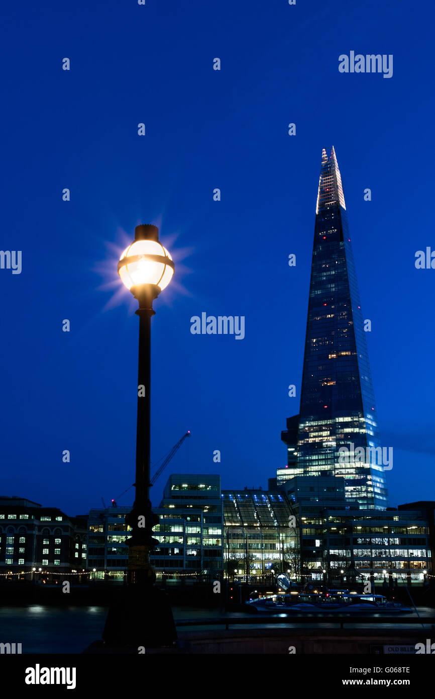 Nacht-Blick auf die Skyline von London zeigt The Shard und eine Straßenlaterne Stockbild