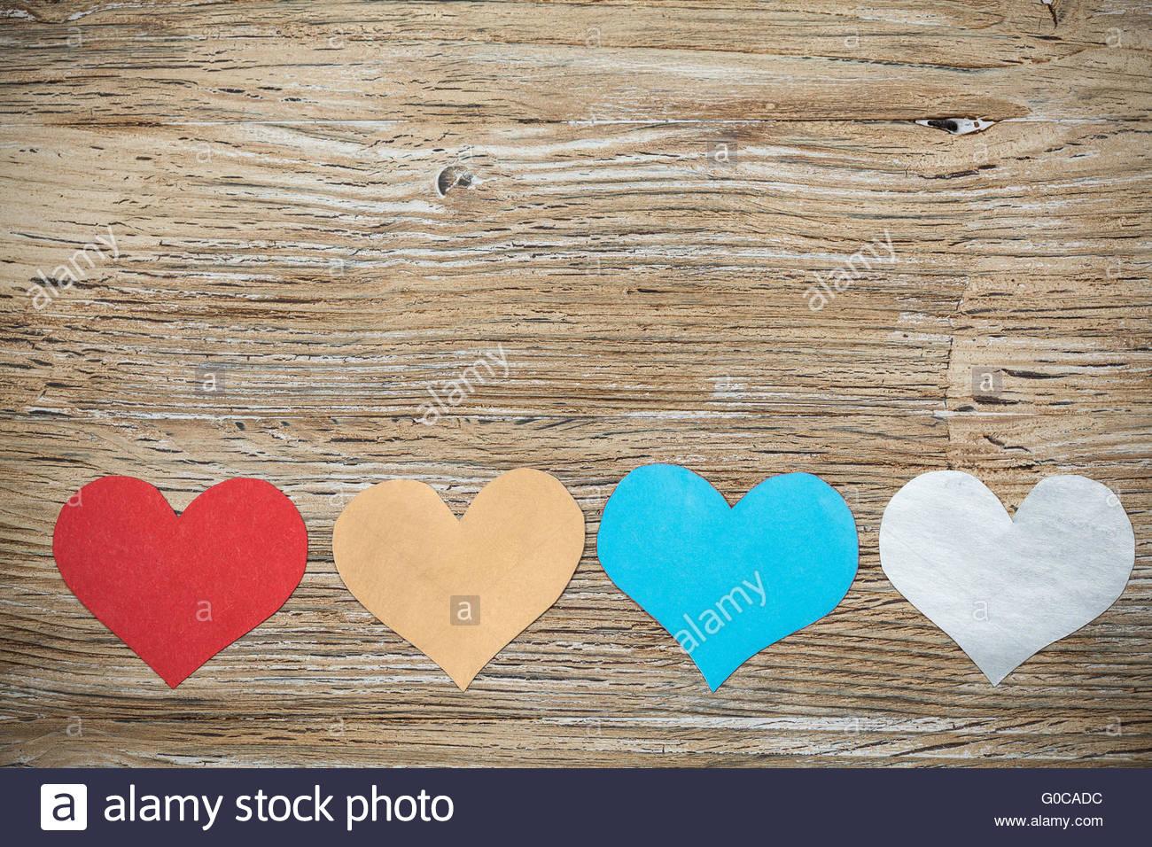 Bunte Papierherzen auf Holz Hintergrund Stockbild