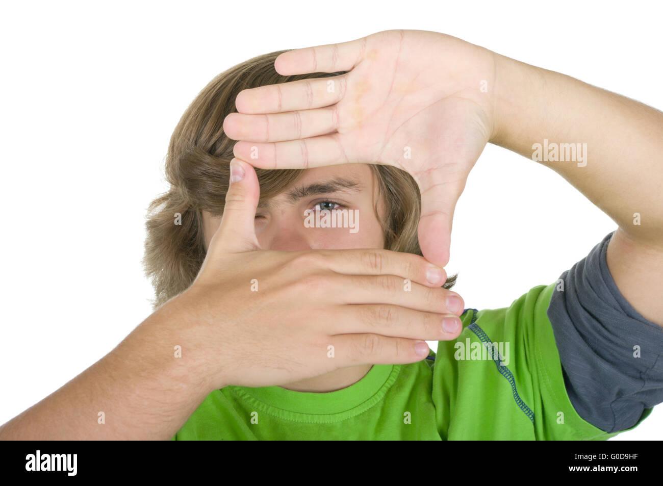 Teenager schaut durch einen Rahmen aus Händen Stockbild