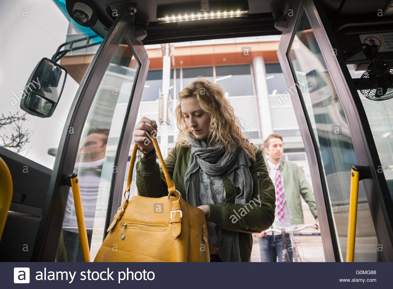 Frau auf der Suche in Handtasche im Bus Tür Stockbild