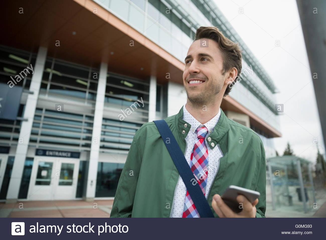 Lächelnde Geschäftsmann mit Handy vor Bahnhof Stockbild
