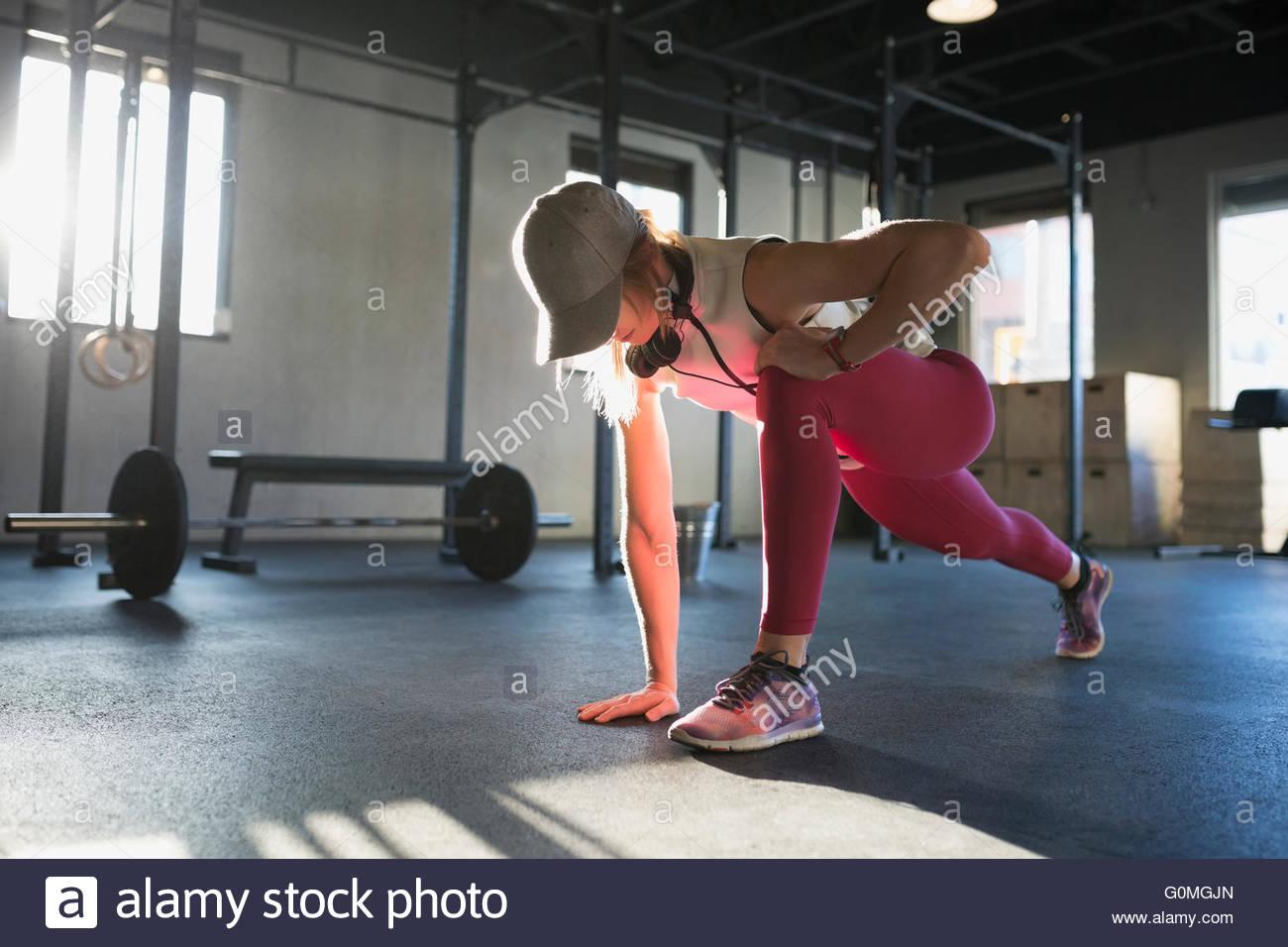 Frau tut Läufer Ausfallschritt in Turnhalle Stockbild