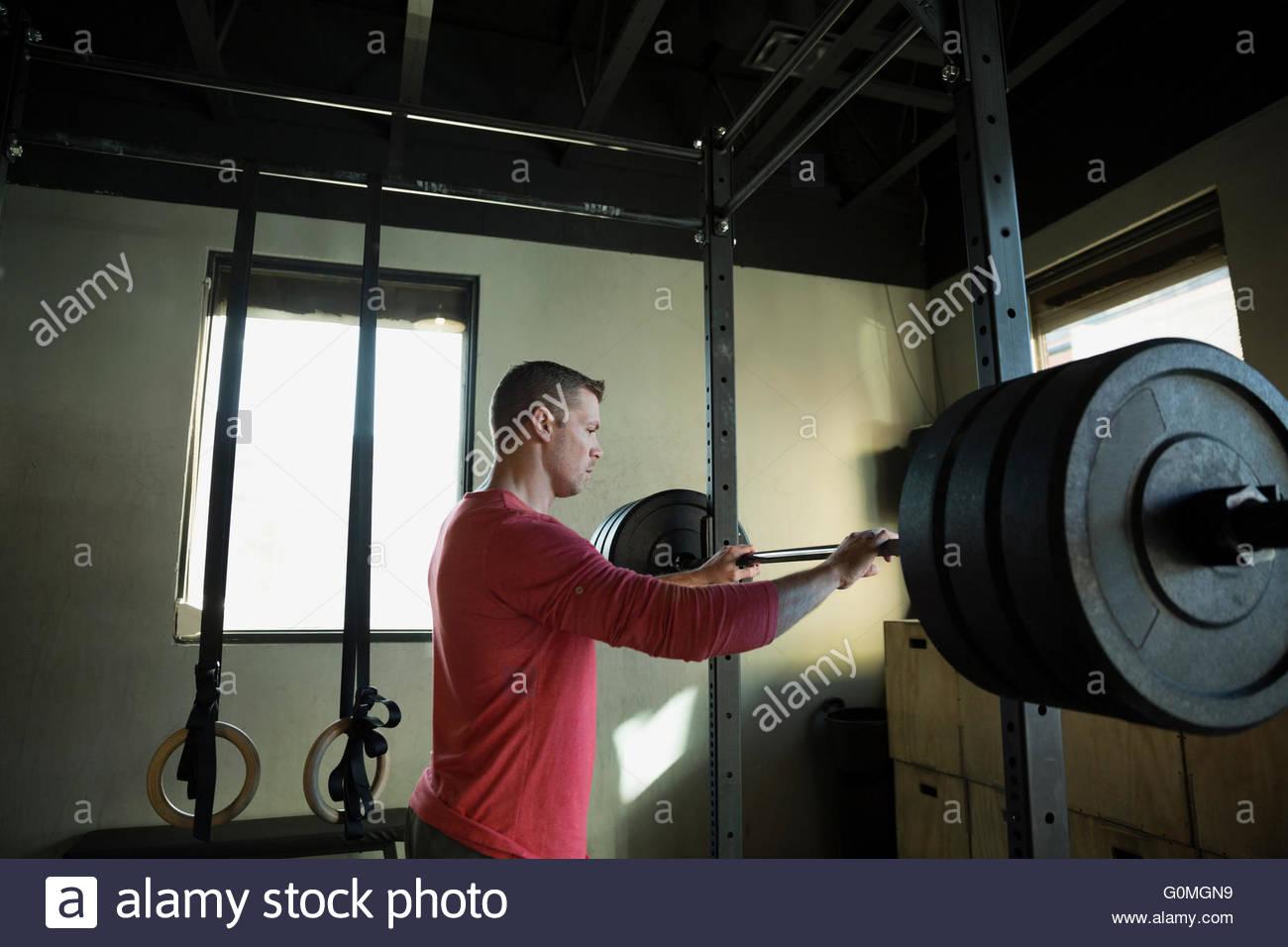 Mann steht auf hocken Hantelablage in Turnhalle Stockbild