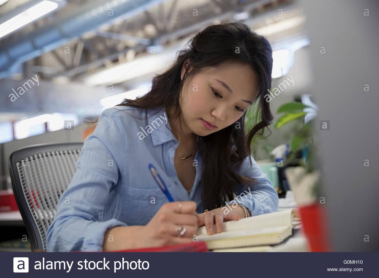 Geschäftsfrau in Fachzeitschrift am Schreibtisch Stockbild