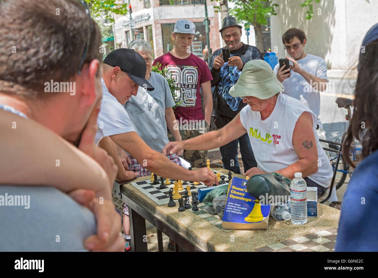 Asheville, North Carolina - Schauspieler Woody Harrelson (schwarze Kappe) spielt Schach in Pritchard Park. Viele Stockbild