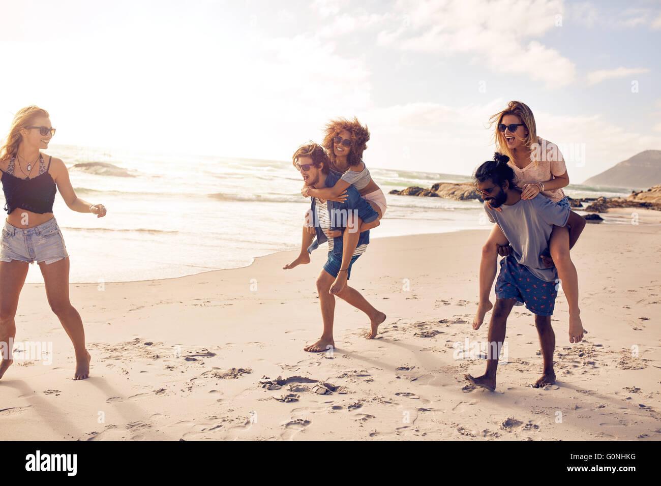 Gruppe von Freunden, die Spaß am Strandurlaub, Männer Frauen Huckepack. Stockbild