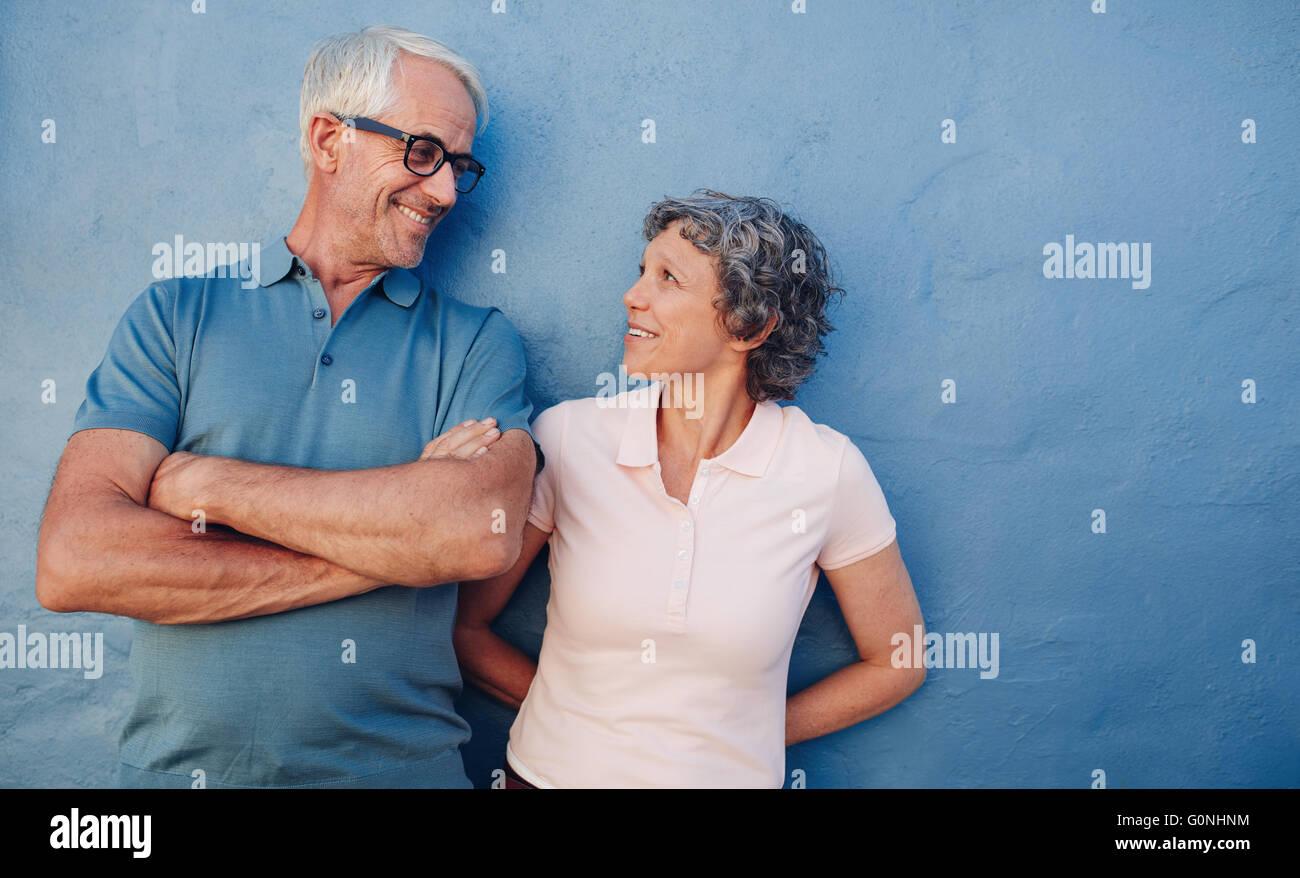 Porträt von liebevollen älteres paar sahen einander vor blauem Hintergrund. Liebevolle Mitte im Alter Stockbild