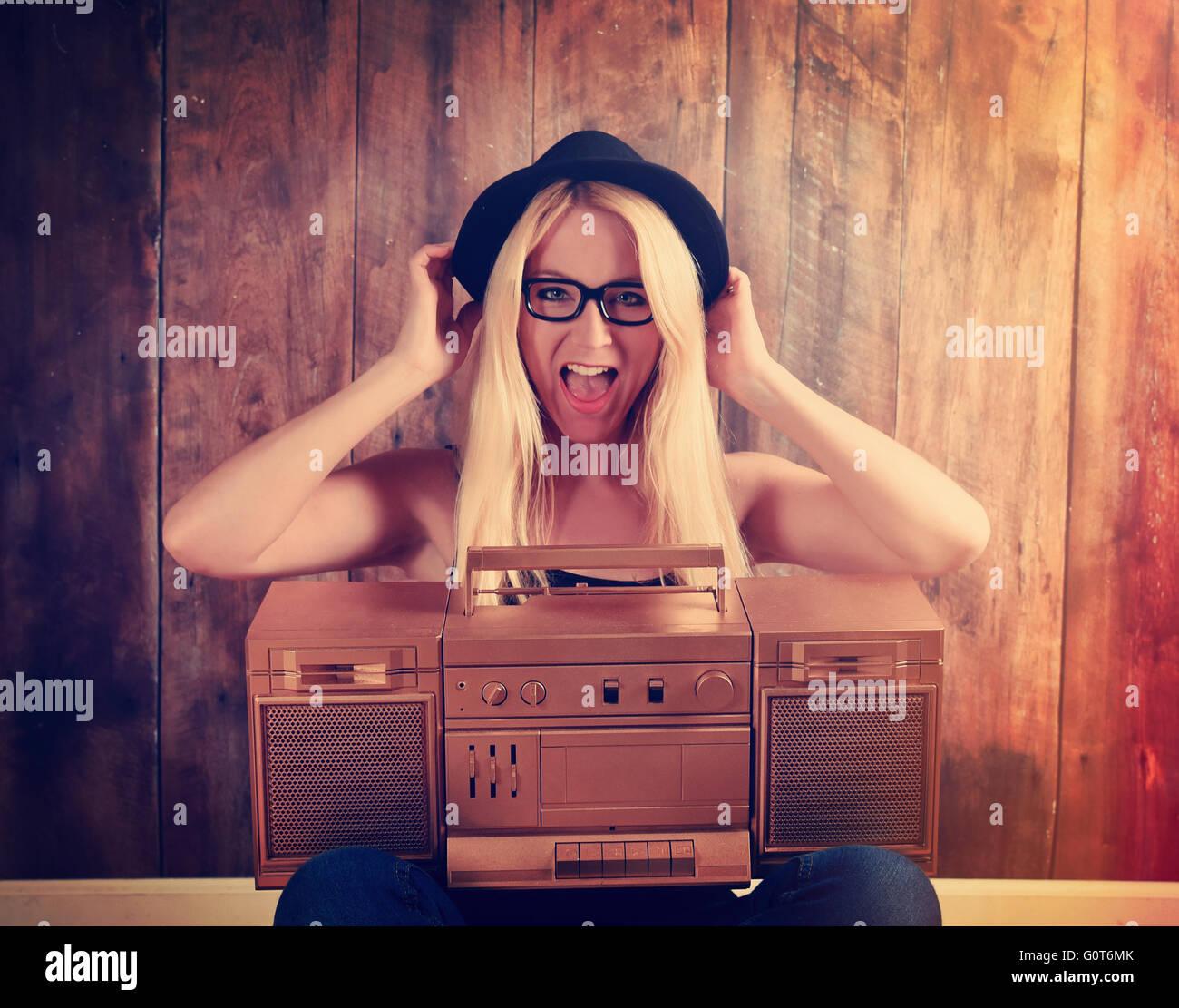 Eine blonde Hipster Mädchen mit Brille ist ein Vintage gold Boombox mit einem Lautsprecher für ein Musik Stockbild