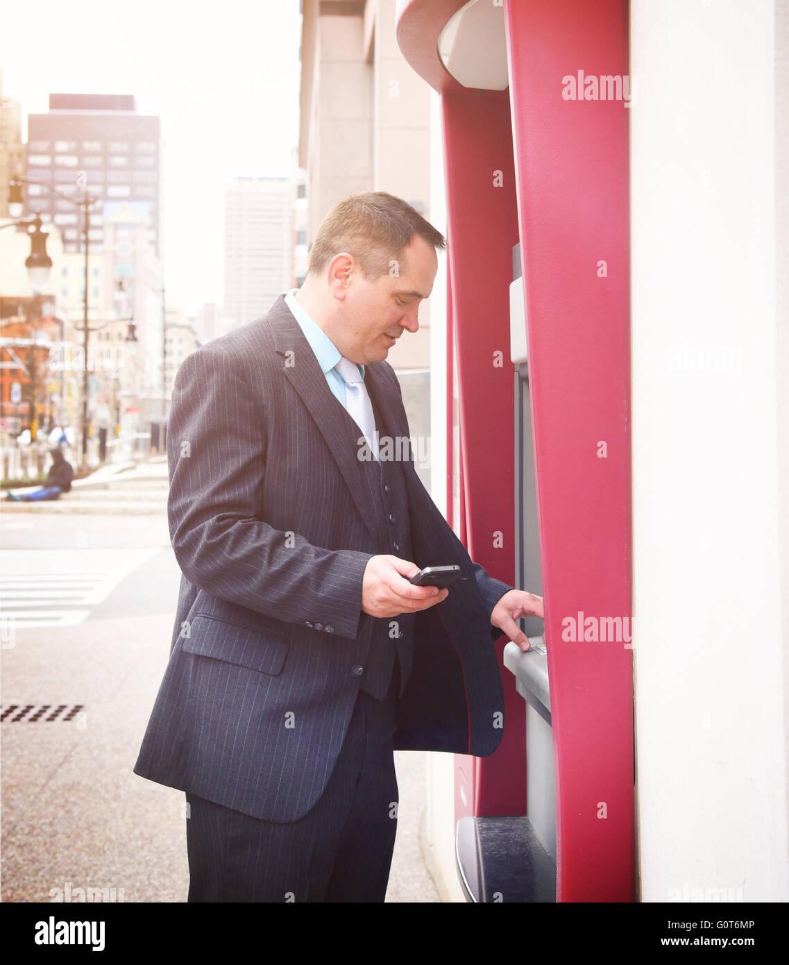 Ein Business-Mann hält eine Telefon und abheben von Geld von seinem Konto an einem Geldautomaten Innenstadt Stockbild