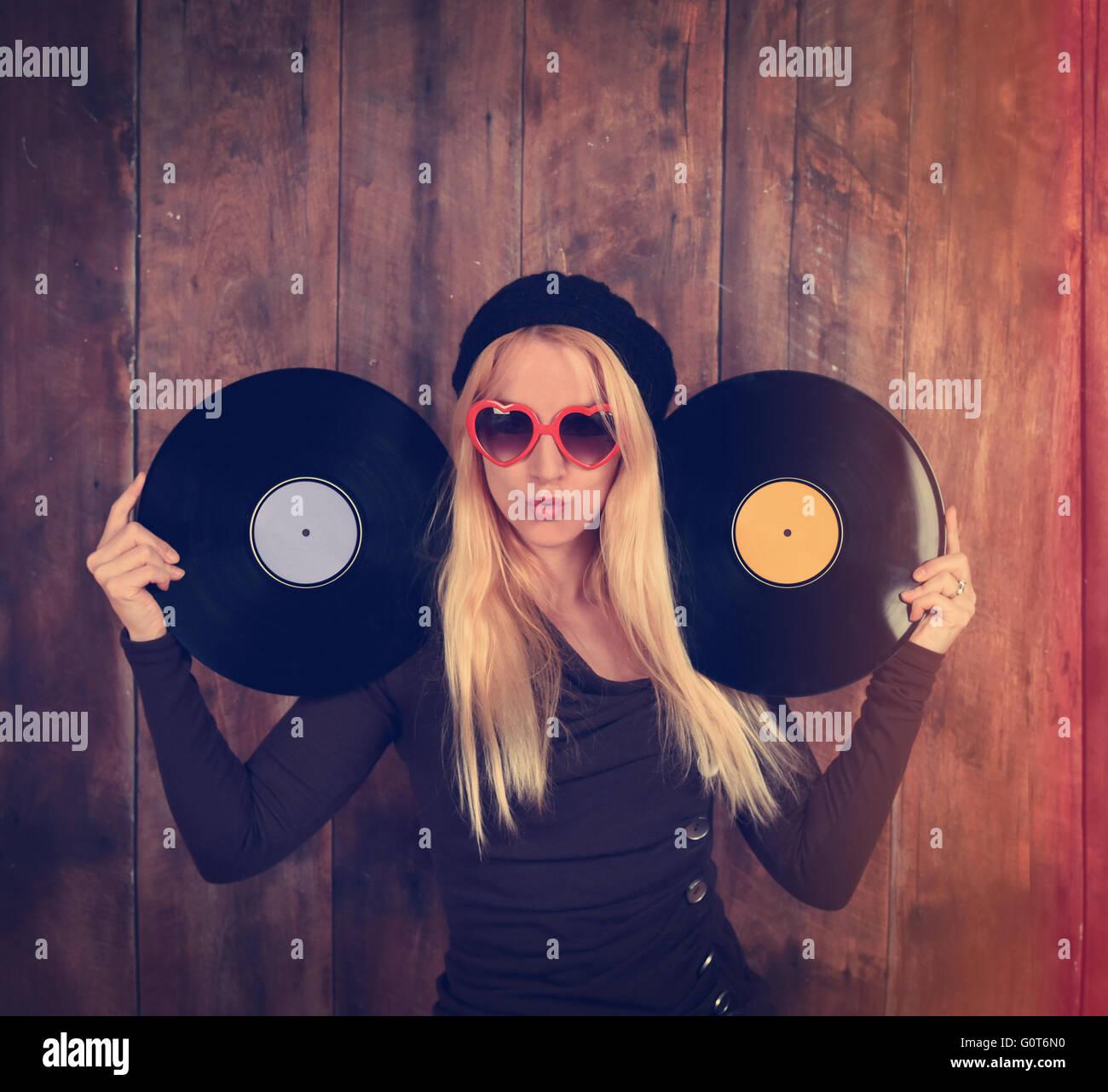 Eine blondes Hipster Mädchen mit Brille hält zwei Vintage Vinyl-Schallplatte für eine Musik-Entertainment Stockbild