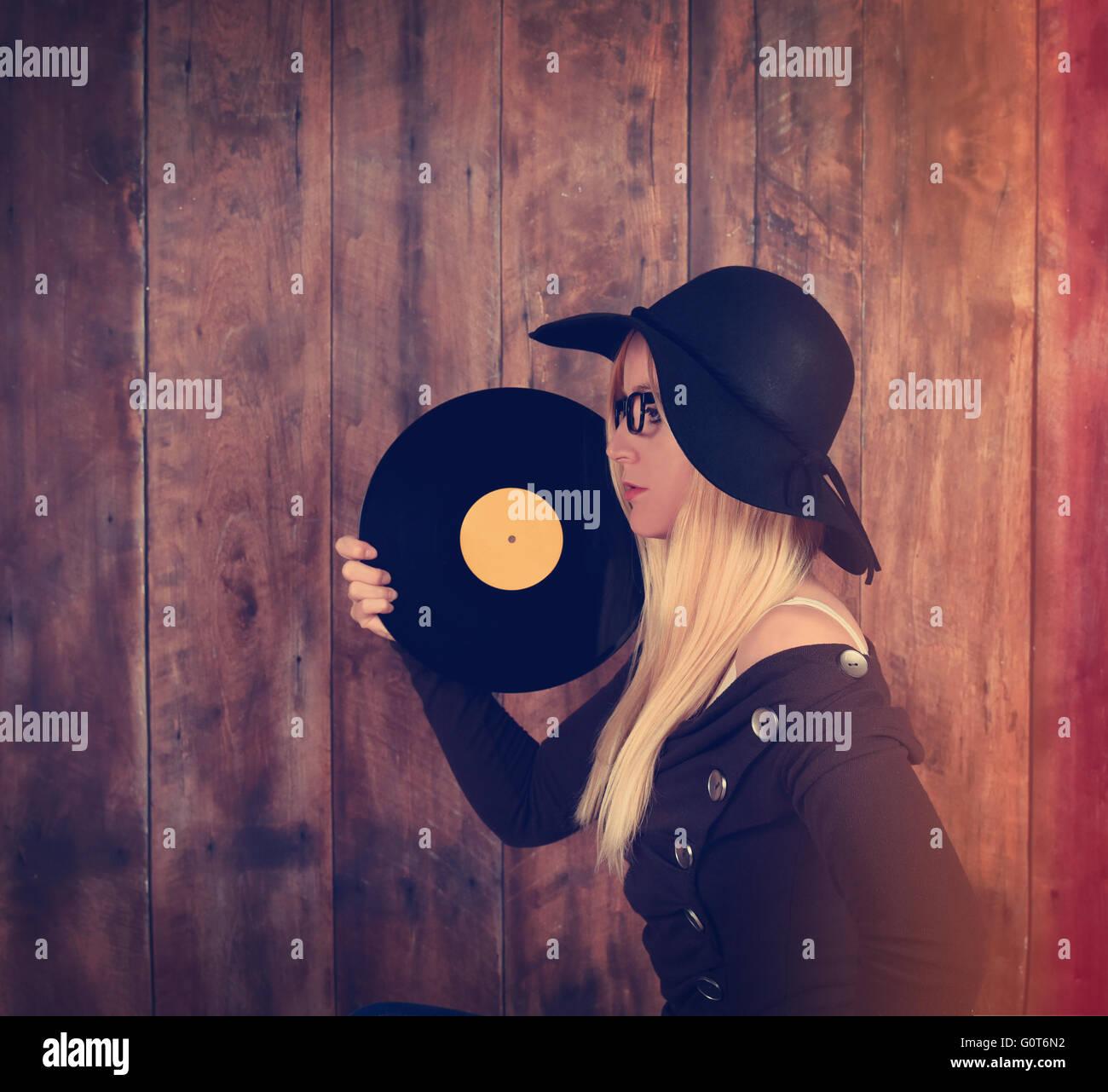 Eine blonde Hipster Mädchen mit Brille hält eine Vintage Vinyl-Schallplatte für eine Musik-Entertainment Stockbild