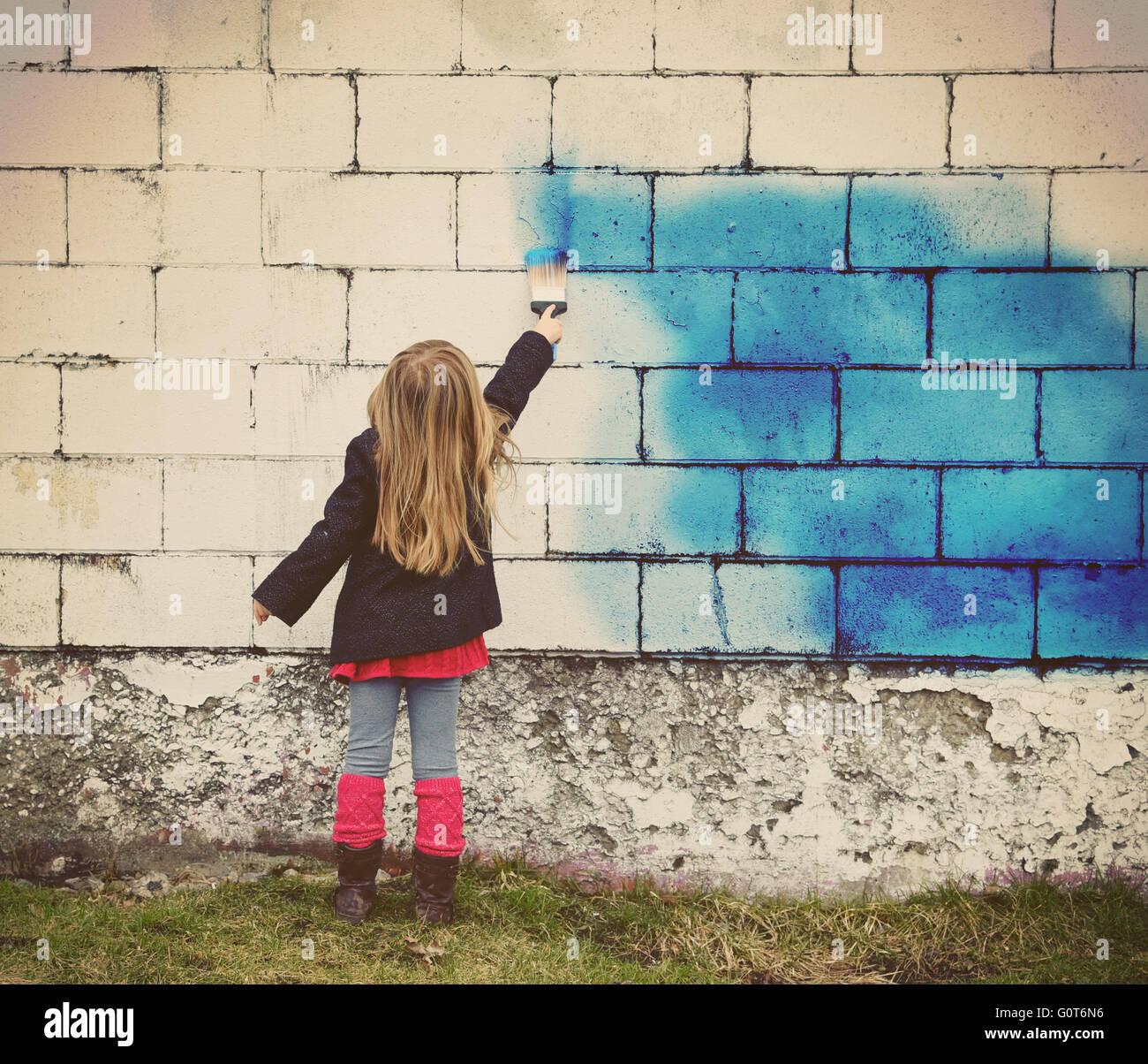 Ein kleines Kind malt eine alte weiße Mauer mit blauer Farbe für kreative Kunst-Konzept oder Design-Idee. Stockbild
