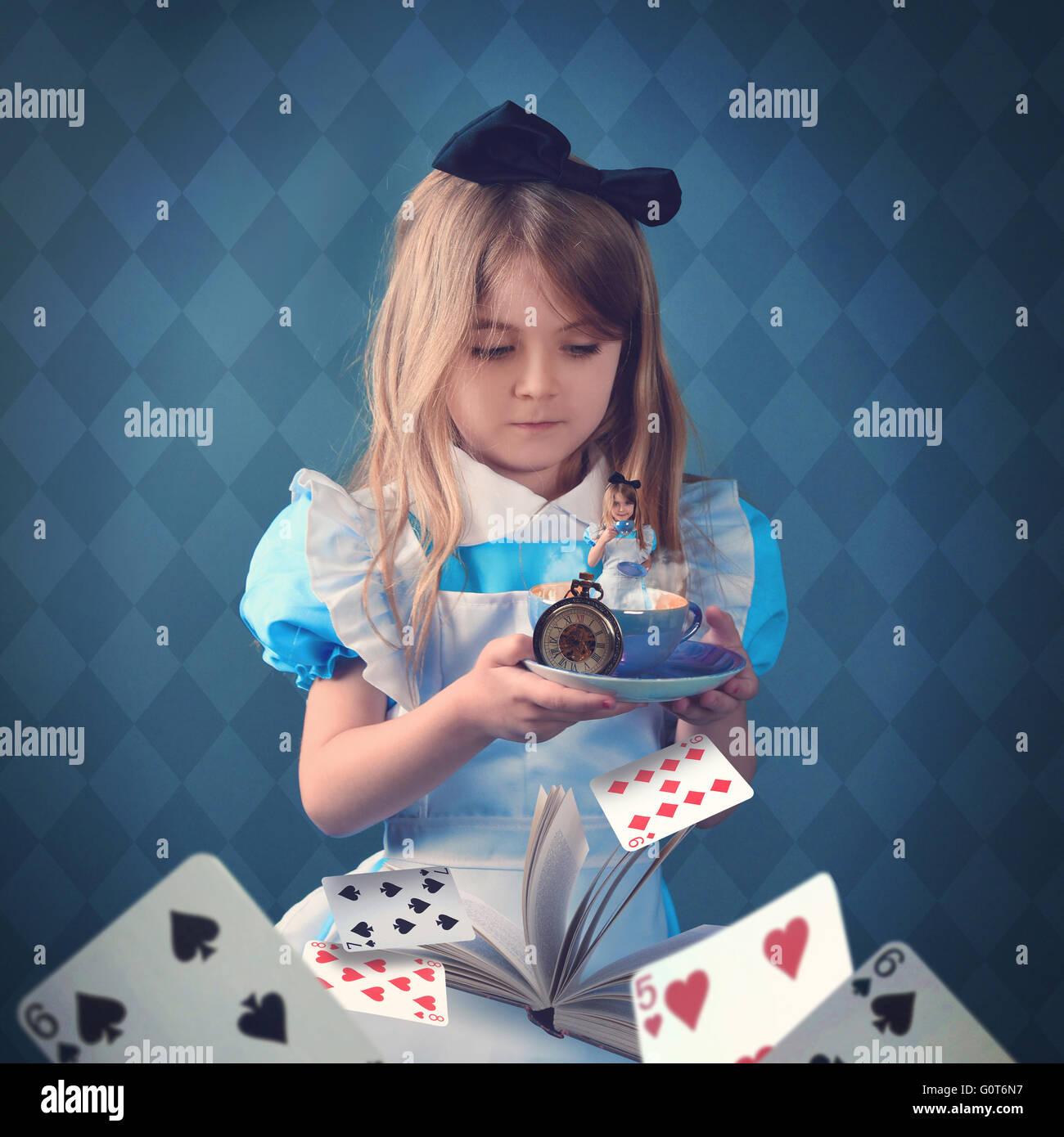 Ein kleines Mädchen hält eine Teetasse mit Spielkarten und ein Buch. Das Kind ist in der Tasse für Stockbild