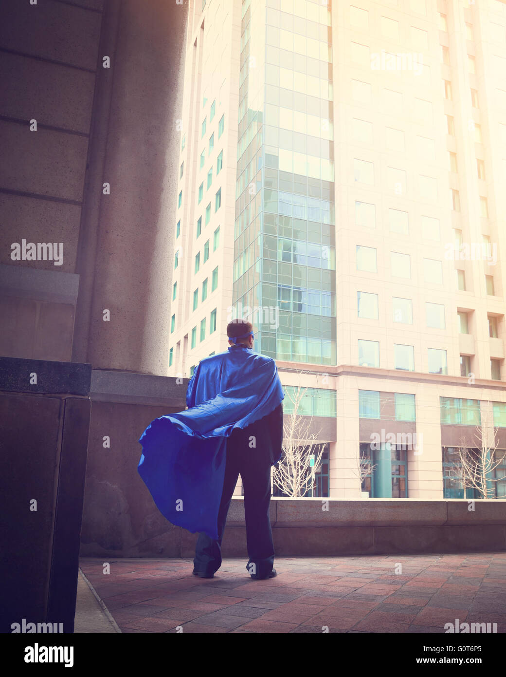 Ein Business-Mann trägt ein super Cape steht in einer Stadt für ein Erfolg, Stärke oder macht Karriere Stockbild