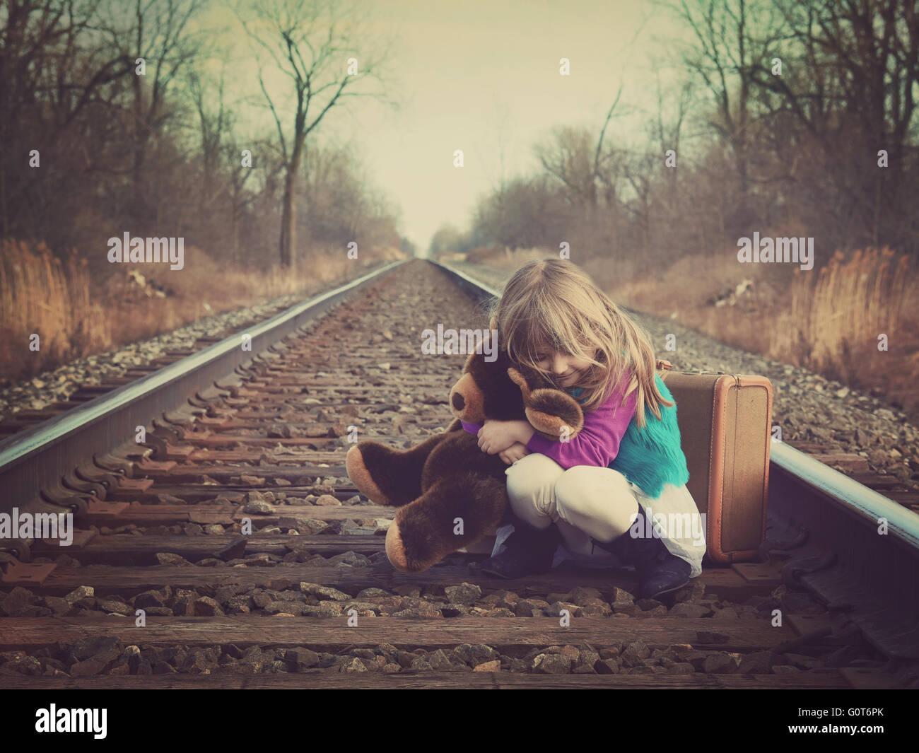 Ein kleines Mädchen sitzt auf einer alten Bahnstrecke außerhalb und umarmt einen Teddybären für ein Vintage Speicher Stockfoto