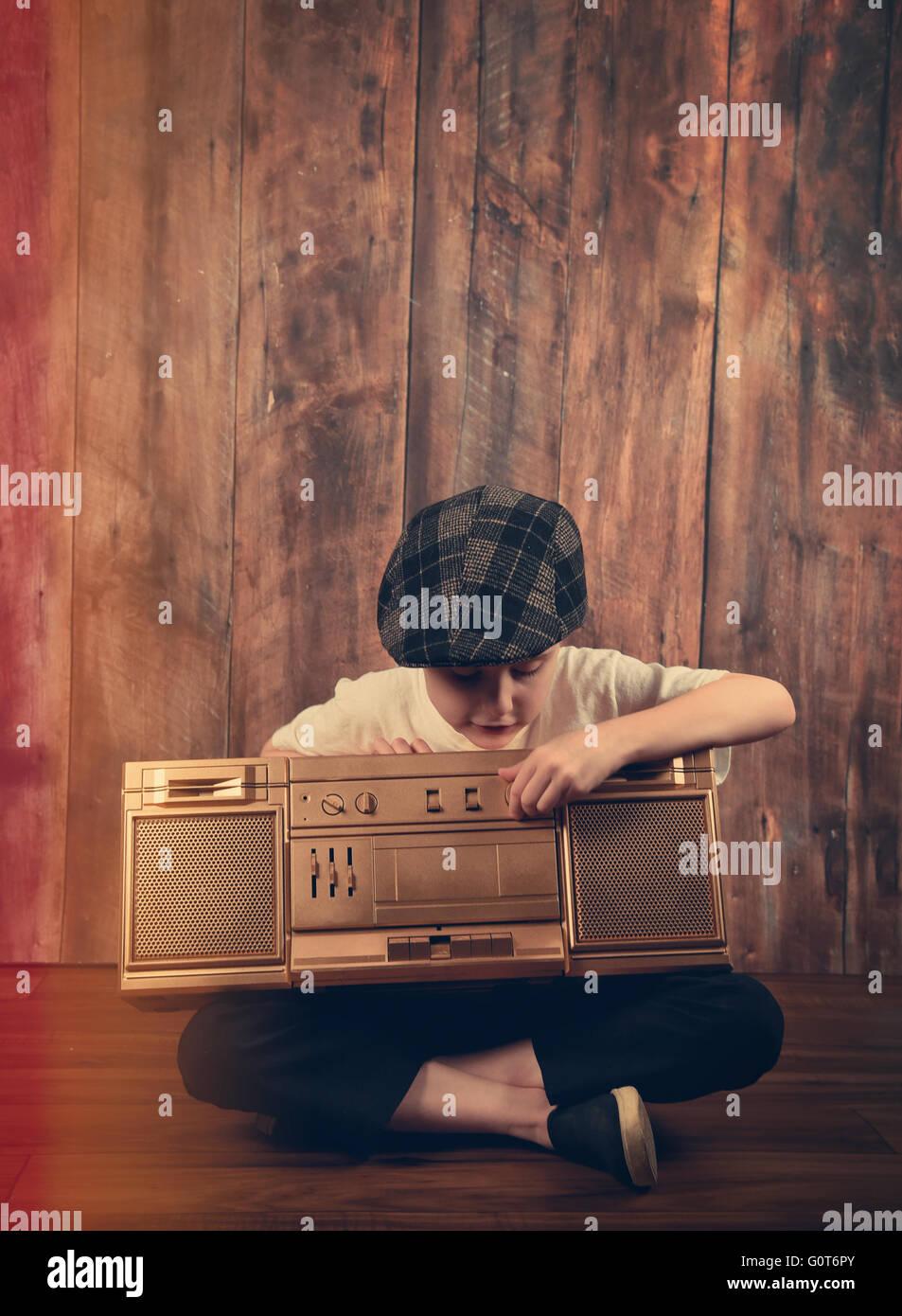 Ein Kind hört ein gold Vintage Stereomusik Boombox mit Holz Hintergrund für eine Unterhaltung oder Audio Stockbild