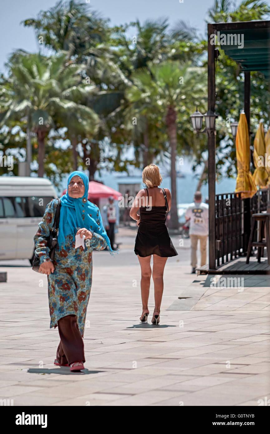 Konzept der Kulturunterschied einer befreiten westlichen Frau und ihrem nahöstlichen Pendant Stockbild