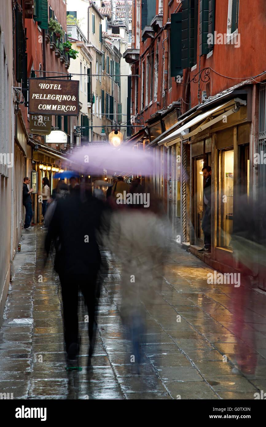 Menschen mit Regenschirmen auf nasser Straße, Venedig, Italien Stockbild