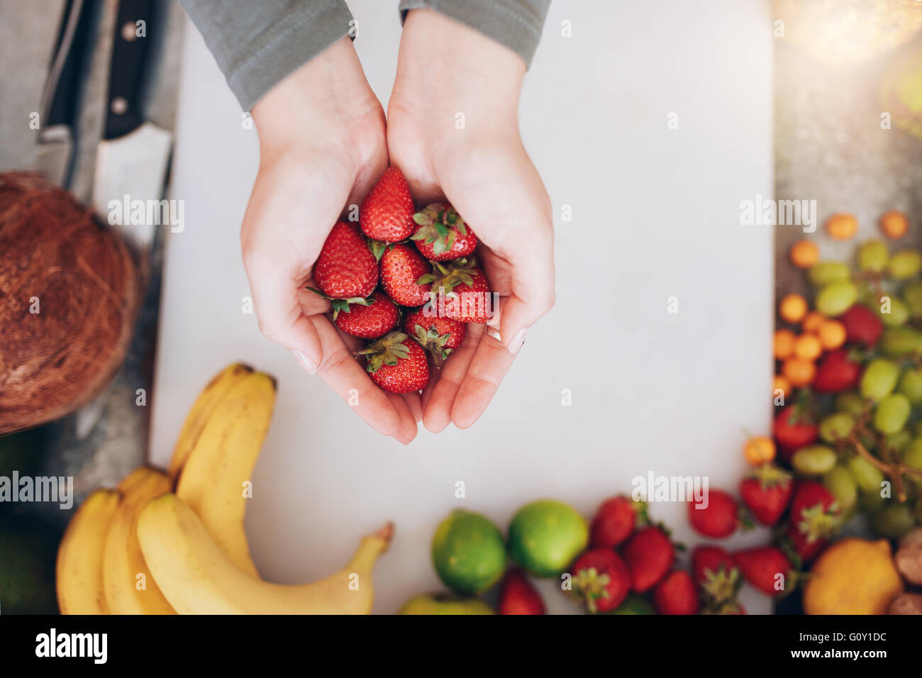 Draufsicht Nahaufnahme Schuss von einer Frauenhand mit frischen Erdbeeren über shopping Board mit Früchten. Stockbild