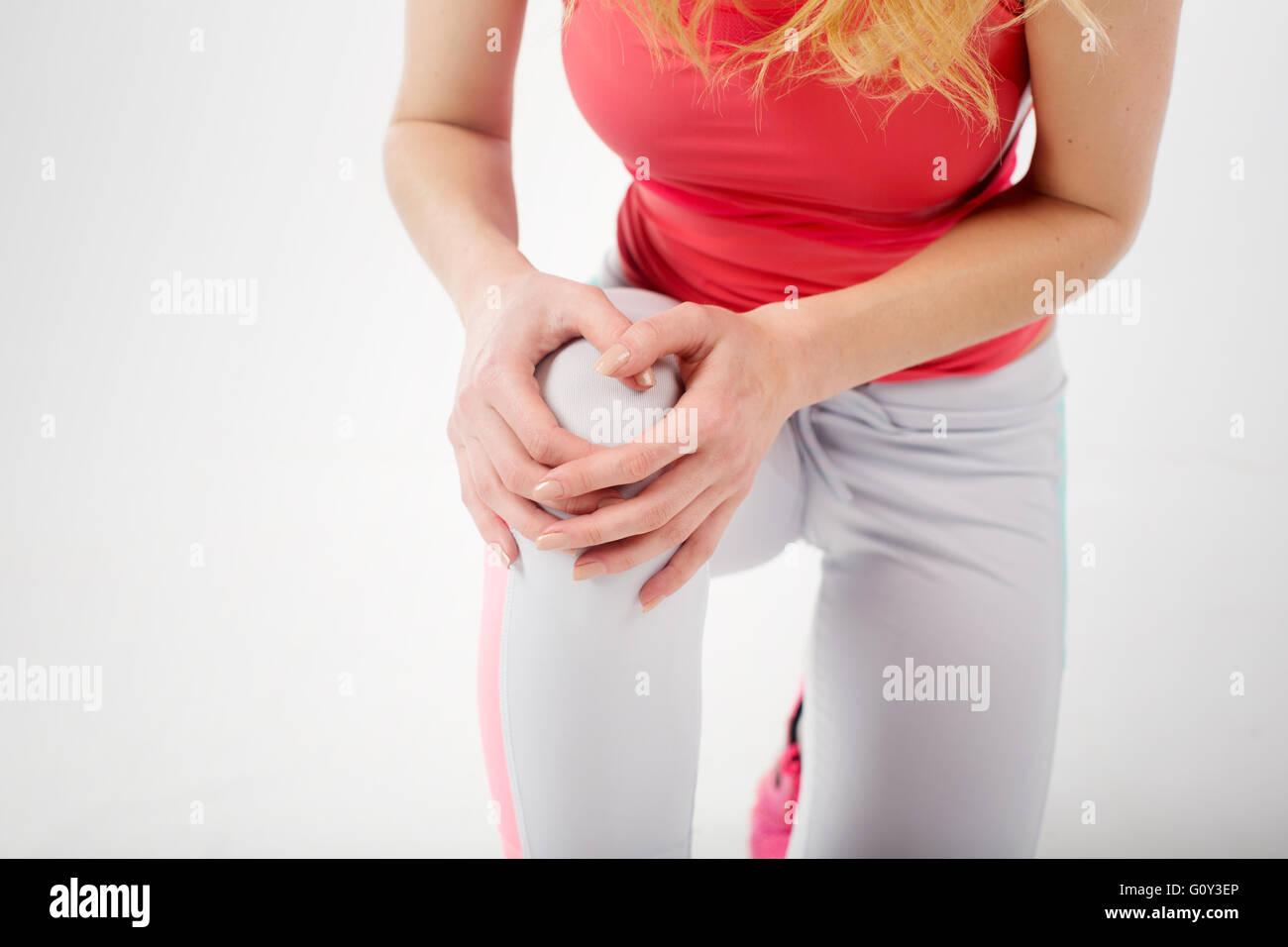 Nahaufnahme der Sportlerin in Fitnesskleidung holding Knie Schmerzen Stockfoto