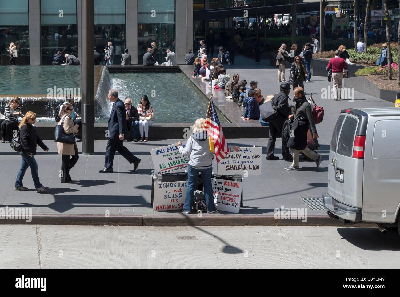 Menschen gehen vorbei an einer einsamen weiblichen amerikanischen Demonstrant / Aktivist in New York mit amerikanischen Stockbild