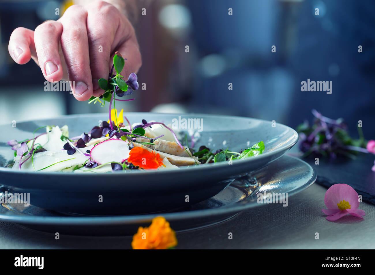 Küchenchef im Hotel oder Restaurant Küche kochen, nur die Hände. Er arbeitet an der Mikro-Kraut-Dekoration. Stockbild