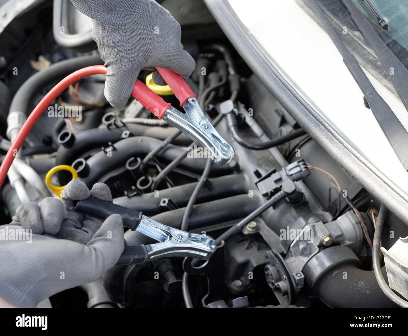 Mechaniker arbeiten an einem Automotor mit elektrischen Kabeln Stockbild