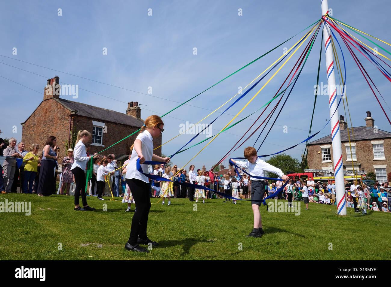 Kinder bereiten die Bänder vor dem Tanz um den Maibaum in Commissioners Maifeiertag festival Stockbild