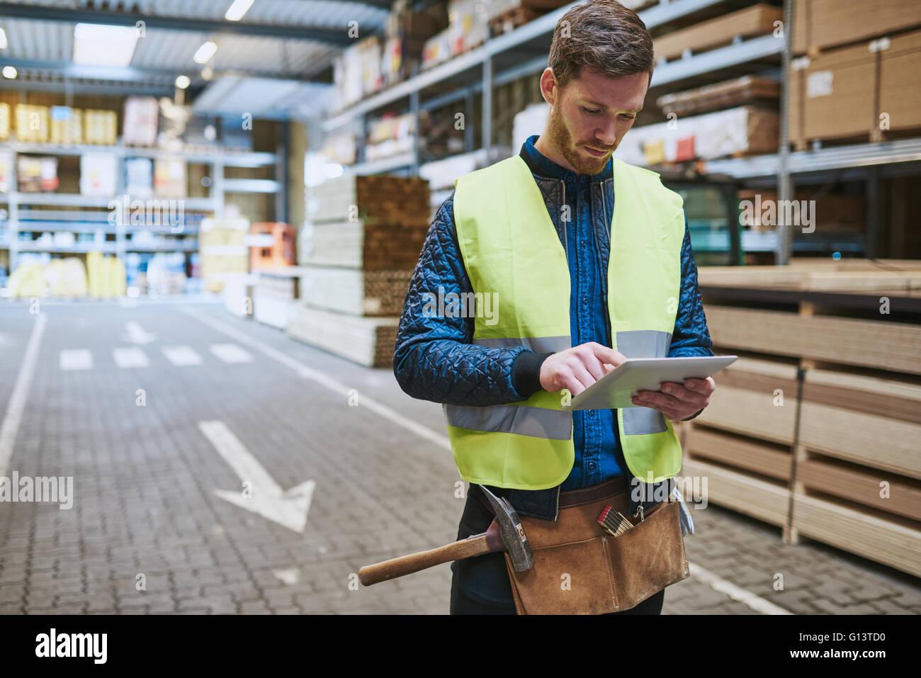 Junge Lagerarbeiter Umgang in Gebäude liefert in einer Fahrt durch Beratung ein Handheld Tablet-PC Stockbild