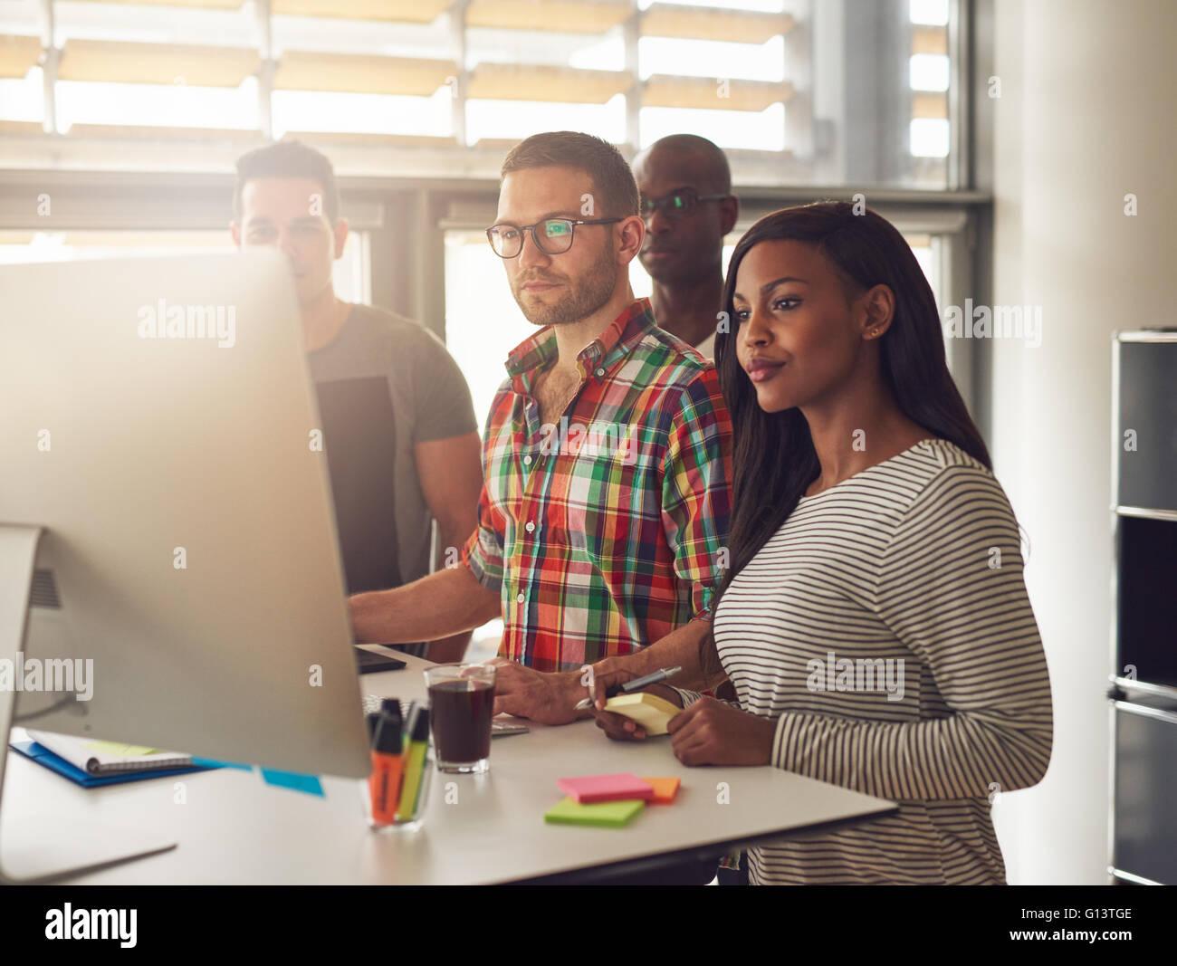 Gruppe von vier schwarzen, kaukasischen und hispanischen Erwachsenen Unternehmer tragen legere Kleidung stehen neben Stockbild