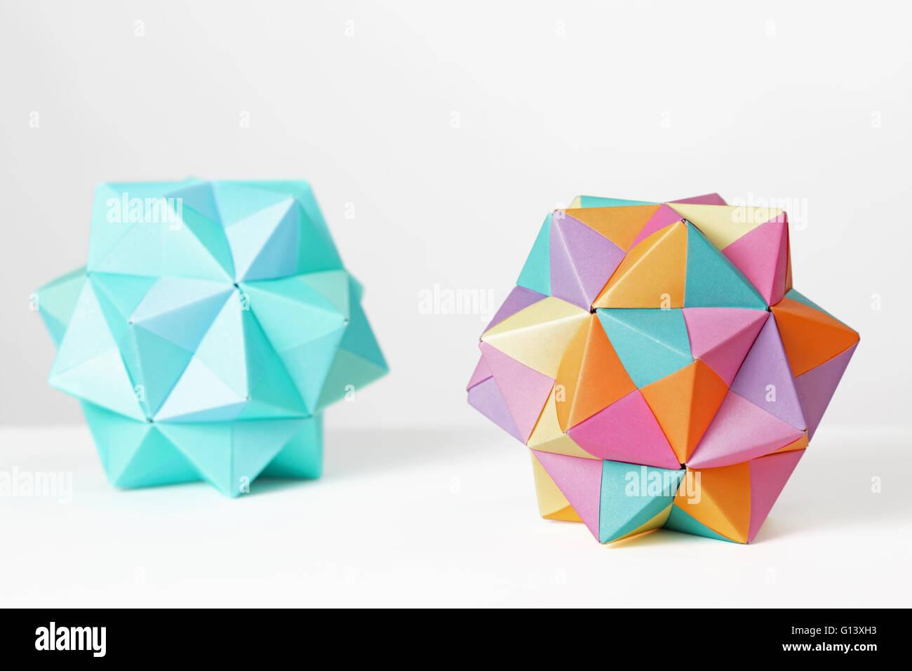 Zwei bunte modulare Origami Ikosaeder gefaltet in Papier auf weißem Hintergrund. Jedes Modul basiert auf einem Stockbild