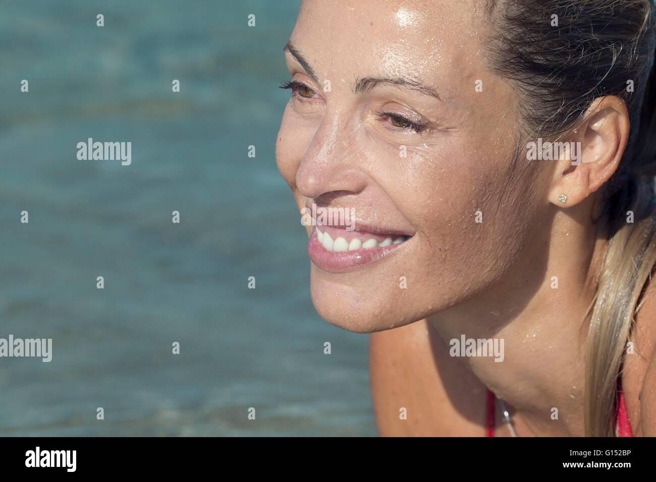 Nahaufnahme von Profil lächelnden blonden Frau im Wasser liegend Stockbild