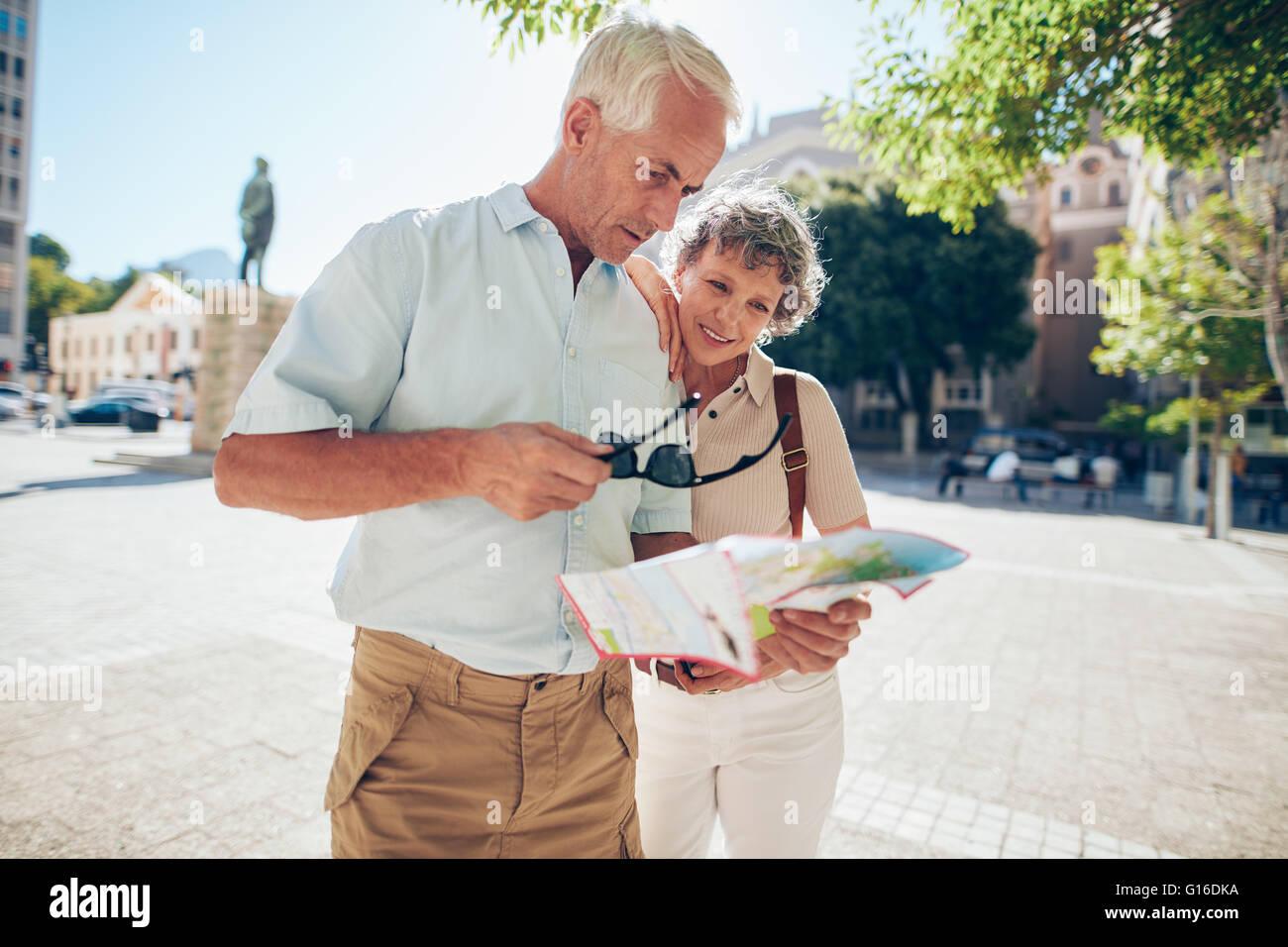 Reifen Sie paar stehen draußen in der Stadt, Blick auf eine Karte. Ältere Mann mit seiner Frau mit Stadtplan Stockbild